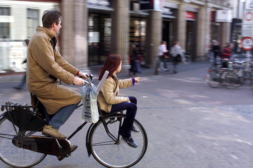Een man fietst met zijn dochter voorop door Utrecht.<br /> <br /> A man is cycling with his daughter at the front in Utrecht.