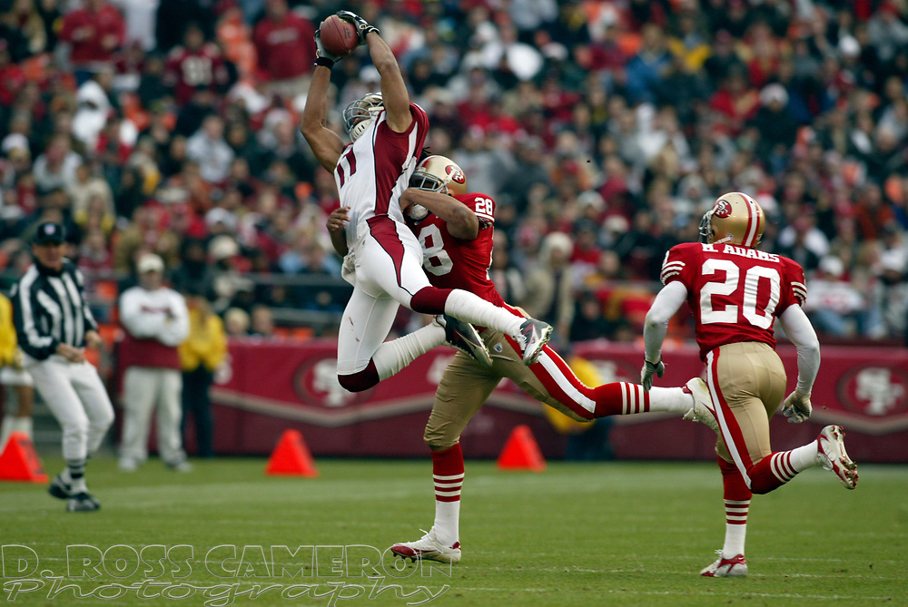 Arizona Cardinals wide receiver Larry Fitzgerald (11) makes a circus catch in front of San Francisco 49ers defenders Keith Lewis (28) and Mike Adams (20), in the third quarter of their NFL football game, Sunday, Dec. 24, 2006 at Candlestick Park in San Francisco.  The Cardinals won, 26-20. (D. Ross Cameron/The Oakland Tribune)
