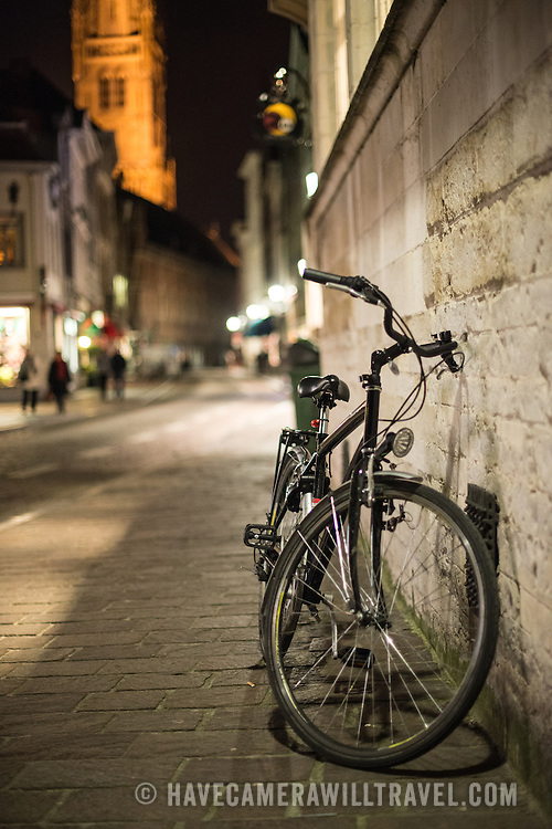 A bicycle rests against a wall of a bilding on a street in the historic center of Bruges, Belgium.