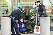 An enviroment protester who has glued herself to a door is spoken to by police officers in front of the entrance of Shell oil HQ on 15th April 2019 in London, United Kingdom.  Extinction Rebellion a climate change protest group are protesting  across the centre of London and plan to block traffic for the next five days.