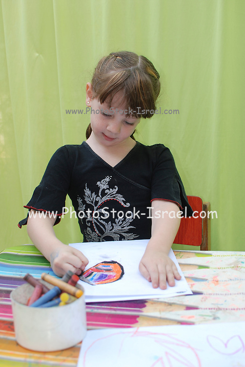 Preschool girl of 5 entertaining herself while drawing