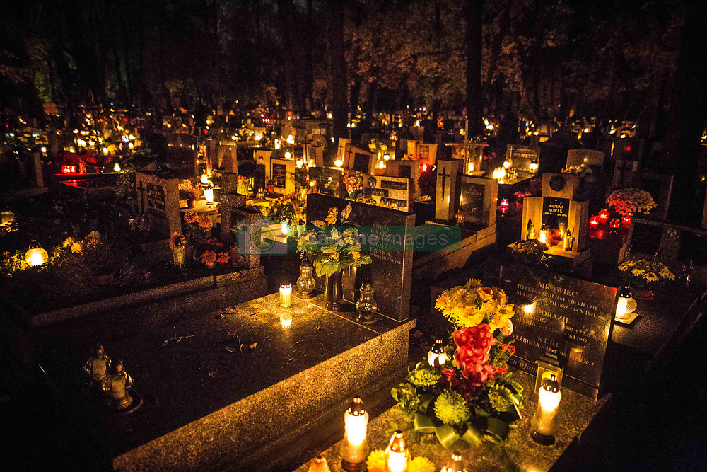 October 31, 2018 - Cracow, Poland - The Rakowicki Cemetery, located in Krakow, is one of the most famous Polish cemeteries, where many Polish notables are buried. It was built in the early nineteenth century On November 1, the day of the feast of All Saints, the Poles deposit millions of candles on the graves throughout the country. A tradition which marks the importance accorded in Poland to the memory and resurrection of the dead. Faithful to tradition, believers or non-believers, all come to the Rakowicki cemetery to place lanterns on the graves. Faithful to tradition, believers or nonbelievers, all come to the cemetery to place lanterns on the graves. Faithful to tradition, believers or nonbelievers, all come to the cemetery to place lanterns on the graves. All Saints' Day is the most important holiday of the Catholic calendar, just like Christmas and Easter. The cemetery is literally covered with flowers and candles. (Credit Image: © Sadak Souici/Le Pictorium Agency via ZUMA Press)