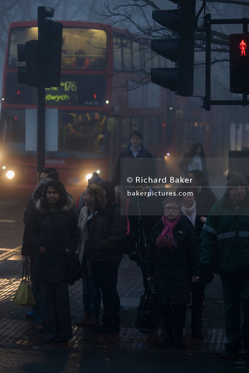 Pedestrians wait to cross in front of commuter traffic at dawn on a foggy morning in south London.