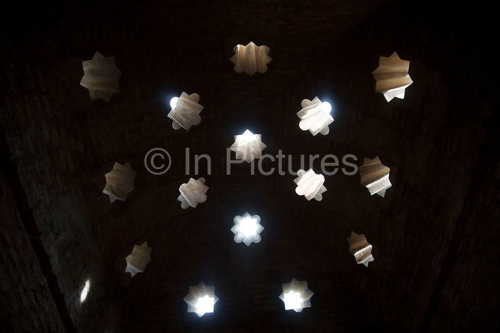 The Alhambra Palace and fortress complex located in Granada, Andalucia, Spain. Muslim / Moorish design cut through the stone of the roof over the Mosque Baths.