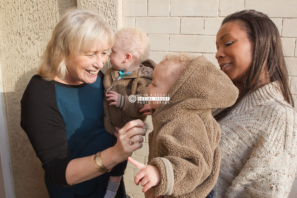 Mother with twins handing over children at childminder's. (This photo has extra clearance covering Homelessness, Mental Health Issues, Bullying, Education and Exclusion, as well as the usual clearance for Fostering & Adoption and general Social Services contexts,)
