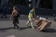 A workman pushes cardboard destined for recycling<br /> in Leadenhall Street, on 12th September, in the City of London, UK.