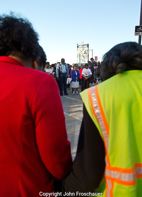 """The crowd holds hands while singing """"We Shall Overcome"""" lead by Stephanie Ann Johnson, after marching across the 11th St. bridge in Tacoma in honor of the 50th anniversary of the """"Bloody Sunday"""" march in Selma Alabama, on Sunday, March 8, 2015. (Photo/John Froschauer)"""