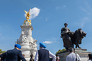 TwoSikhs wearing blue turbans stand in front of the Victoria memorial at Buckingham Palace on the 29th August 2019 in London in the United Kingdom.