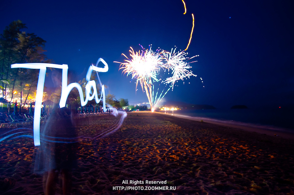 Girl lightpaints the word Thai, Phuket, Thailand