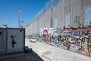 Original Banksy street art next to the partition wall which annexes Palestinian land to Israel in the West Bank city of Bethlehem on 1st April 2016 in Bethlehem, West Bank. During the Palestine Marathon, thousands of runners, both professional and amateur come from across the globe to take part in the Right to Movement event.