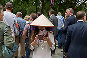 A lady wearing an Asian conical hat uses a phone to text a message during the 100th anniversary of the Royal Air Force RAF, on 10th July 2018, in London, England. The Asian conical hat, commonly known as an Asian rice hat, coolie hat or farmers hat, is a simple style of conical hat originating in East, South, and Southeast Asia, particularly Bangladesh, Bhutan, China, Cambodia, India, Indonesia, Japan, Korea, Laos, Malaysia, Myanmar, Nepal, Philippines, parts of Russian Manchuria and Vietnam.