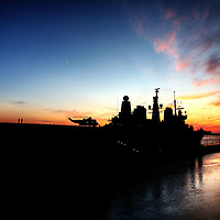 Sunset and HMS Ark Royal sits as a silhouette by Liverpool.  Two men can be seen on the flight deck enjoying the sunset.