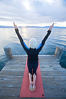 Young woman doing yoga on pier in Tahoe City, CA