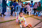 """A Cambodian child waits for his parents to finish registering for temporary Thai ID cards at the temporary """"one stop service center"""" in the Bangkok Youth Center in central Bangkok. Thai immigration officials have opened several temporary """"one stop service centers"""" in Bangkok to register undocumented immigrants and issue them temporary ID cards and work permits. The temporary centers will be open until August 14."""
