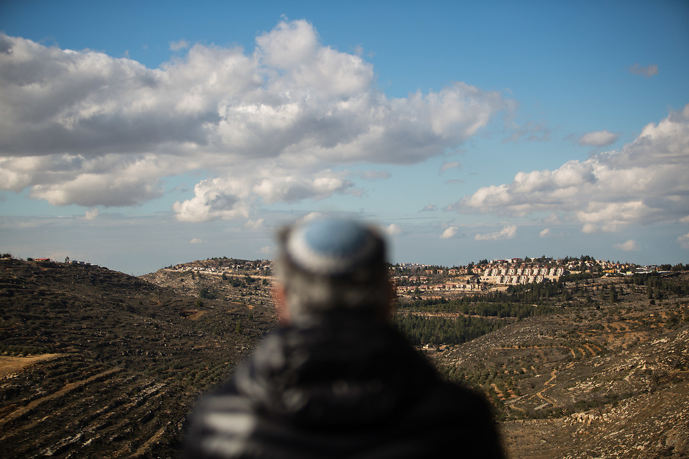 A Jewish man wearing a yarmulke or a kippa, the traditional Jewish skullcap for men, watches a general view of the West Bank Jewish settlement of Eli from the archaeological park of Ancient Shiloh, which is located at the entrance to the modern Jewish settlement of Shiloh, south of the Palestinian West Bank town of Nablus, on January 1, 2017.
