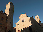 Stone tower and the Collegiata di San Gimignano, the main church, at Piazza Duomo, the main square in the medieval town San Gimignano, a UNESCO Heritage site in Tuscany, Italy