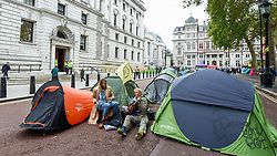 © Licensed to London News Pictures. 08/10/2019. LONDON, UK.  Climate activists in a makeshift camp in Horse Guards Road outside HM Treasury, on day two of Extinction Rebellion's protest which is planned to close-down Westminster and other areas in the capital for two weeks.  Demonstrators are calling on the Government's immediate action to tackle the negative effects of climate change.  Photo credit: Stephen Chung/LNP