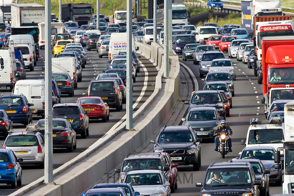 Cars and a motorcyclist in traffic congestion on M25 motorway, near London, United Kingdom
