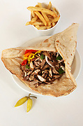 Shawarma shavings in a Lafa -  flat Iraqi pita with pickles and french fries. A popular fast food in Israel and the Middle East
