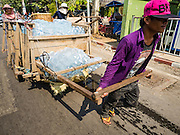 """15 FEBRUARY 2016 - ARANYAPRATHET, SA KAEO, THAILAND:  A Cambodian porter in Aranyaprathet pulls a load of bottled water to the Cambodian side of the border. Thais selling bottled water in the border town of Aranyaprathet, opposite Poipet, Cambodia, have reported a surge in sales recently. Cambodian officials told their Thai counterparts that because of the 2016 drought, which is affecting Thailand and Cambodia, there have been spot shortages of drinking water near the Thai-Cambodian and that """"water shortages in Cambodia had prompted people to hoard drinking water from Thailand.""""    PHOTO BY JACK KURTZ"""