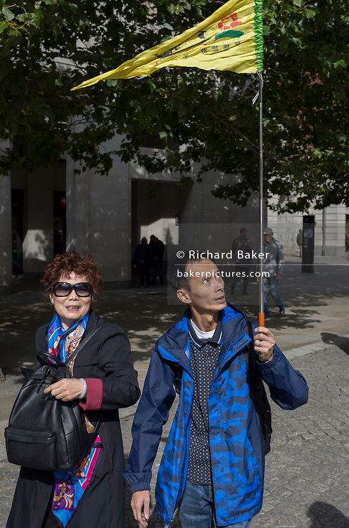 An Asian tour leader holds up a flag for followers to see clearly, outside St. Paul's Cathedral, on 14th September 2017, in the City of London, England.