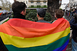 © Licensed to London News Pictures. 06/04/2019. LONDON, UK.  Members of the LGBT community wear a rainbow flag during a protest outside the Brunei-owned Dorchester Hotel in reaction to reports that the Sultan of Brunei decreed that adultery and gay sex is punishable by death by stoning in the Islamic sultanate.  Several large clients of the Dorchester Hotel have already ceased bookings in response to the decree.  Photo credit: Stephen Chung/LNP