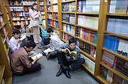 Customers sit on the floor and read in a popular book shop in Shanghai. China's state media said recently that nearly half of the media products such as books, films, music CDs and software bought by Chinese consumers in 2005 were pirated.