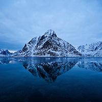 Olstind mountain peak rises from fjord, Reine, Lofoten Islands, Norway