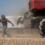 Alan Stoner, 21, cleans a combine with an air compressor during wheat harvest near Hamer, Idaho, August 2017.