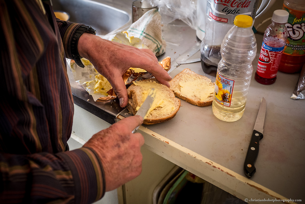 (2013)  Father Hermann fixes some sandwiches for a woman who seeks his help at his home at the church in Pioneers Park.