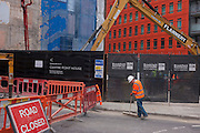 A workman employed on a construction site for the delveloper Brookfield in central London, sweeps the dust from an entrance gate.