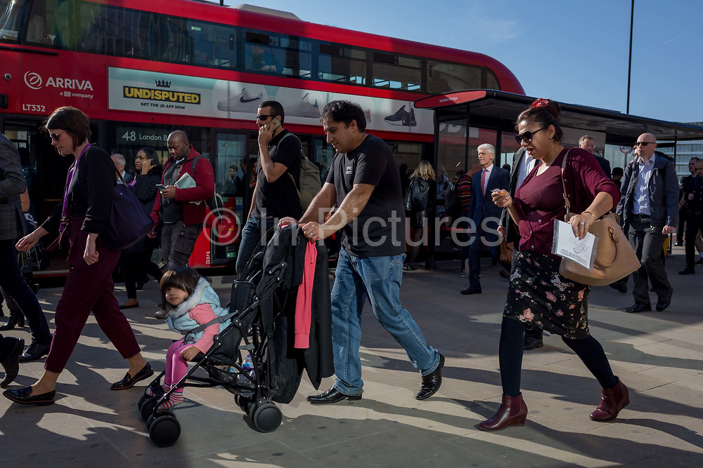 A man pushes a child in her buggy while commuters and other pedestrians walk over London Bridge, the oldest of the capitals crossing over the river Thames between the capitals financial district, the City of London, and Southwark on the south bank, on 15th May 2018, in London, UK.