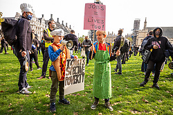 © Licensed to London News Pictures. 19/10/2020. London, UK. Two children of hospitality workers left, Xavi 8 and Ramsey 9 (permission granted) dress up in chef's outfits and hold posters at a protest by hospitality workers in Parliament Square against tougher Covid restrictions and the amount of financial compensation given to the industry. Today, Wales's First Minister Mark Drakeford has announced a two week 'firebreaker' for Wales with shops, bars, pubs and cafes to closed and people ordered to stay at home from this Friday pilling pressure on Prime Minister Boris Johnson to follow suit in England as coronavirus levels of infections continue to escalate throughout the UK. Photo credit: Alex Lentati/LNP