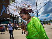 23 JUNE 2016 - MAHACHAI, SAMUT SAKHON, THAILAND:   A man dressed as a traditional Burmese street performer rests while waiting for Aung San Suu Kyi to arrive in Samut Sakhon, a province south of Bangkok. Tens of thousands of Burmese migrant workers, most employed in the Thai fishing industry, live in Samut Sakhon. Aung San Suu Kyi, the Foreign Minister and State Counsellor for the government of Myanmar (a role similar to that of Prime Minister or a head of government), is on a state visit to Thailand. Even though she and her party won the 2015 elections by a landslide, she is constitutionally prohibited from becoming the President due to a clause in the constitution as her late husband and children are foreign citizens      PHOTO BY JACK KURTZ
