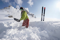 Man shovelling snow for bivouac camp, Tyrol, Austria