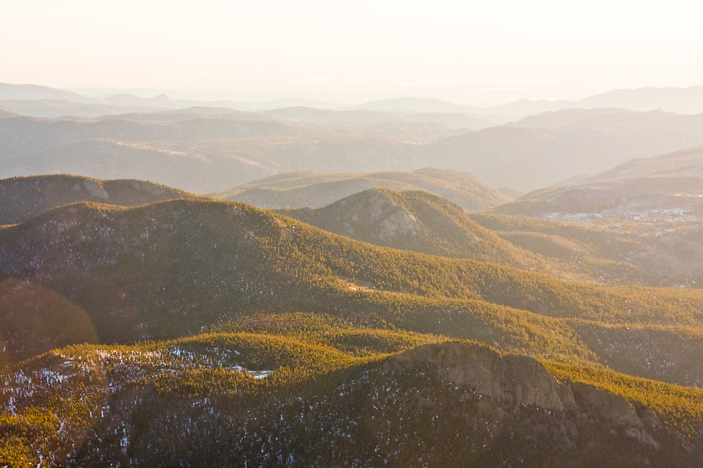 Rolling forested hills backlit at sunrise along the Front Range in Rocky Mountain National Park, Colorado.