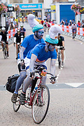Two male cyclist, dressed as blue Smirths riding a vintage tandem bicycle, during the 7th Prudential RideLondon Surrey Classic on the 4th August 2019 in Kingston upon Thames in the United Kingdom.