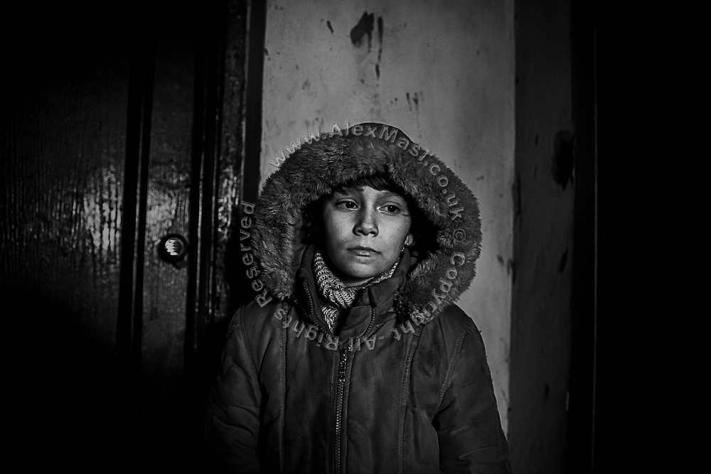 A worried young girl, Zarina, 9, is standing by the entrance of her home in the town of Zaitsevo, near the frontline in eastern Ukraine.