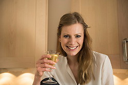 Portrait of a young woman drinking white wine and smiling, Munich, Bavaria, Germany