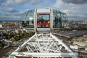Tourists enjoying the view in a pod on the Coca-cola London Eye set against a moody London sky. It is the worlds largest  ferris wheel, situated on the South bank of the River Thames in London. Designed by Marks Barfiled Architects. (photo by Andrew Aitchison / In pictures via Getty Images)