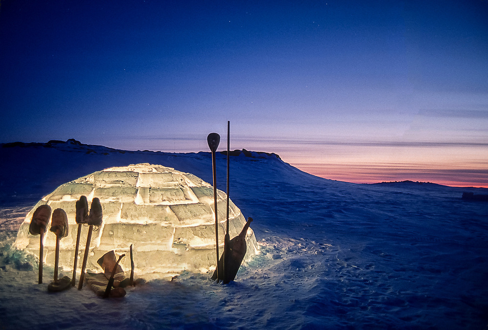 Inuit tools silhouetted  against a lit igloo at dusk outside Baker Lake, Nunavut.