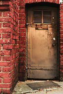 Building entrance with heavy steel doorwar with brick wall