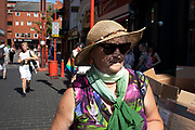 Woman with a straw hat on Gerrard Street, Soho, also known as Chinatown in London, United Kingdom. The present Chinatown is in the Soho area occupying the area in and around Gerrard Street. It contains a number of Chinese restaurants, bakeries, supermarkets, souvenir shops, and other Chinese-run businesses and is in itself a major tourist destination.