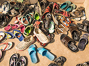 04 MARCH 2014 - MAE SOT, TAK, THAILAND: Students' shoes in front of classroom door at the Sky Blue School. There are approximately 140 students in the Sky Blue School, north of Mae Sot. The school is next to the main landfill for Mae Sot and serves the children of the people who work in the landfill. The school relies on grants and donations from Non Governmental Organizations (NGOs). Reforms in Myanmar have alllowed NGOs to operate in Myanmar, as a result many NGOs are shifting resources to operations in Myanmar, leaving Burmese migrants and refugees in Thailand vulnerable. The Sky Blue School was not able to pay its teachers for three months during the current school year because money promised by a NGO wasn't delivered when the NGO started to support schools in Burma. The school got an emergency grant from the Burma Migrant Teachers' Association and has since been able to pay the teachers.    PHOTO BY JACK KURTZ