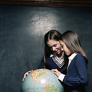 two middle school girls inspect a globe in a classroom setting
