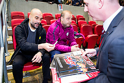 Manchester City manager Pep Guardiola signs matchday programmes for Bristol City head of media Adam Baker - Rogan/JMP - 23/01/2018 - Ashton Gate Stadium - Bristol, England - Bristol City v Manchester City - Carabao Cup Semi Final Second Leg.
