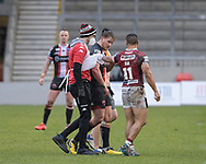 Willie Isa (11) of Wigan Warriors checks in on James Greenwood (21) of Salford Red Devils as he leaves the pitch after an injury