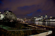 Night scene looking over the River Thames towards the skyline of the City of London financial district. On the left is City Hall, home to local government.