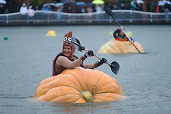 A woman wearing a poop costume races a giant pumpkin across Lake of the Commons at the 14th annual West Coast Giant Pumpkin Regatta in Tualatin, Ore. on October 21, 2017. (Photo by Alex Milan Tracy)
