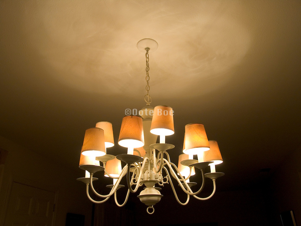 chandelier hanging from ceiling with lights on at night